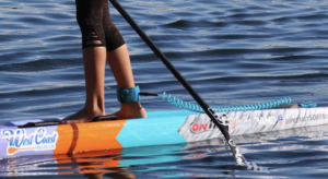 Woman standing on a SUP wearing a leash